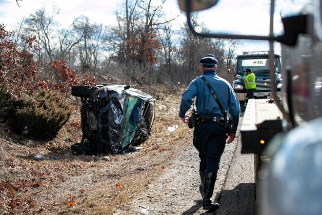 Massachusetts State Police investigate the scene of a rollover crash involving a black Lexus on Route 24 North just prior to exit 20A in Stoughton that resulted in  serious injuries and one fatality on Monday, Jan. 18, 2021.