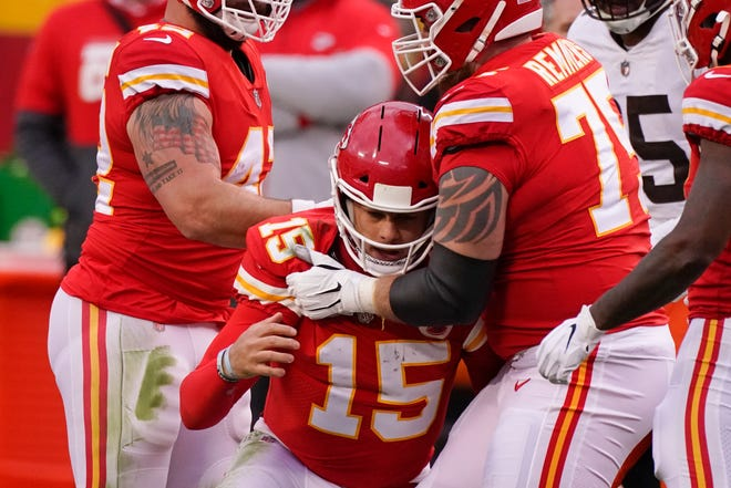 """Kansas City Chiefs quarterback Patrick Mahomes (15) is helped off the field by teammate Mike Remmers, right, after getting injured during the second half of Sunday's playoff game against the Cleveland Browns. Chiefs coach Andy Reid said Mahomes was """"doing good"""" after the Chiefs hung on to claim a 22-17 win despite Mahomes missing much of the second half."""