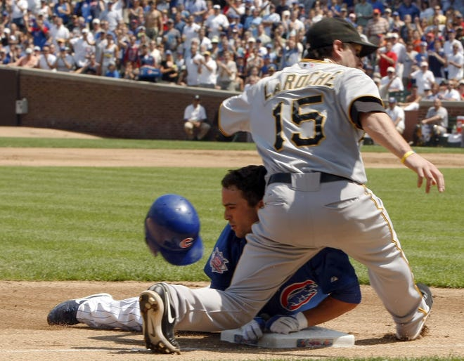 Ex-Chicago Cubs outfielder Sam Fuld slides into third with a triple in the first inning against Pittsburgh Pirates third baseman Adam LaRoche at Wrigley Field in Chicago on Friday, August 14, 2009.