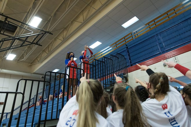 West Henderson's cheerleaders, top, cheer on the volleyball players at a match against North Buncombe earlier this season at West.