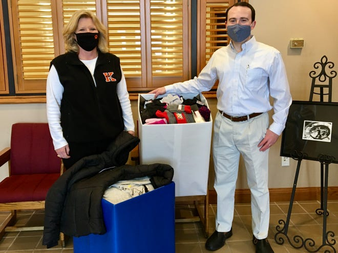 Ashley Young, right, the Kiwanis Club Parade Committee Chair, presents Tricia Reger, Kirksville R-III assistant superintendent, with the donated clothes from the 2020 Christmas parade.