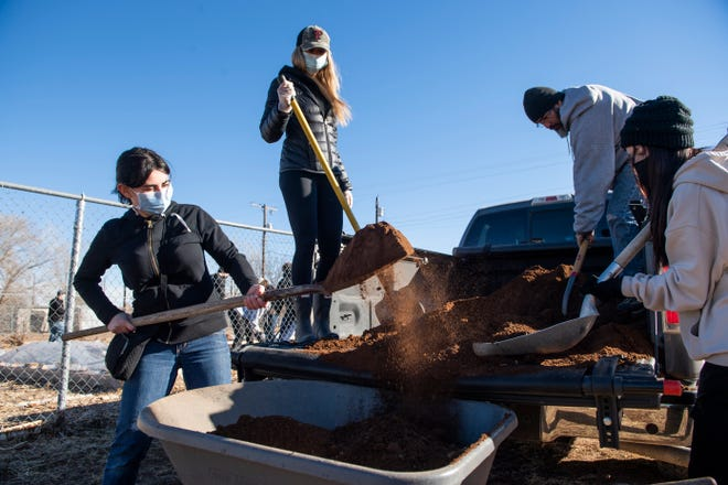Volunteers shovel dirt for the gardens at the Booker T. Washington Community Garden for Martin Luther King Jr. Day on Monday, Jan. 18, 2021, in Lubbock, Texas.