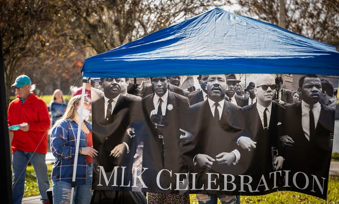 Southeastern University students hang an MLK celebration banner at a booth across the street from The Joinery on Lake Mirror. The food hall hosted a Brunch and Build Community Unifying Event on MLK Day in Lakeland on Monday.