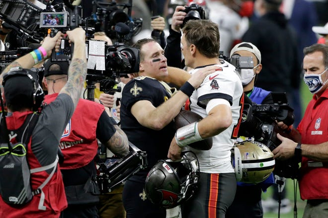 New Orleans Saints quarterback Drew Brees, center left, speaks with Tampa Bay Buccaneers quarterback Tom Brady after an NFL divisional round playoff football game, Sunday, Jan. 17, 2021, in New Orleans. The Buccaneers won 30-20.