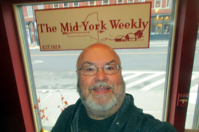 Mike Jaquays poses Jan. 7 in front of the Mid-York Weekly sign at the newspaper's Hamilton office, which will be closing for good at the end of the month thanks to the coronavirus. The paper itself will continue thanks to modern remote technology.