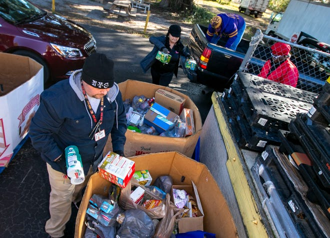 Volunteers and Interfaith Emergency Services staff unload some of the boxes of food donated Monday in honor of the Rev. Martin Luther King Jr.