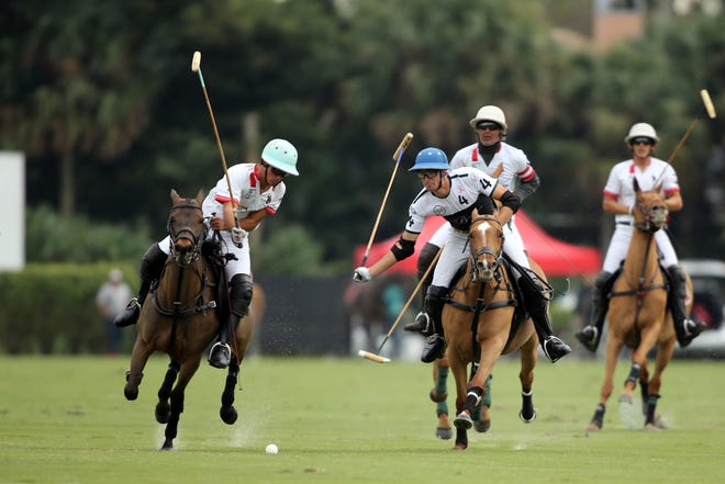 Santa Clara's Keko Magrini (left) and Beverly Equestrian's Hilario Figueras battle  for the ball during Sunday's match at International Polo Club Palm Beach.