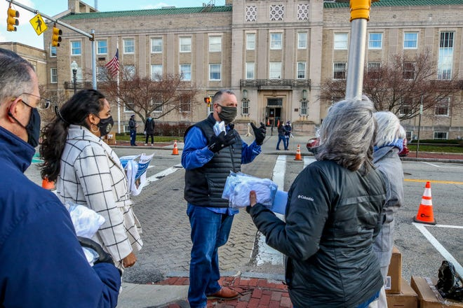 Pawtucket Mayor Donald Grebien chats with volunteers outside City Hall on Monday. He joined the volunteers to hand out free masks to the community as part of a service day in memory of the work done by the Rev. Martin Luther King Jr.