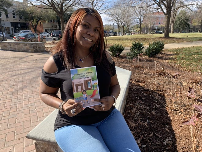Shelly Lewis proudly shows her new children's book.