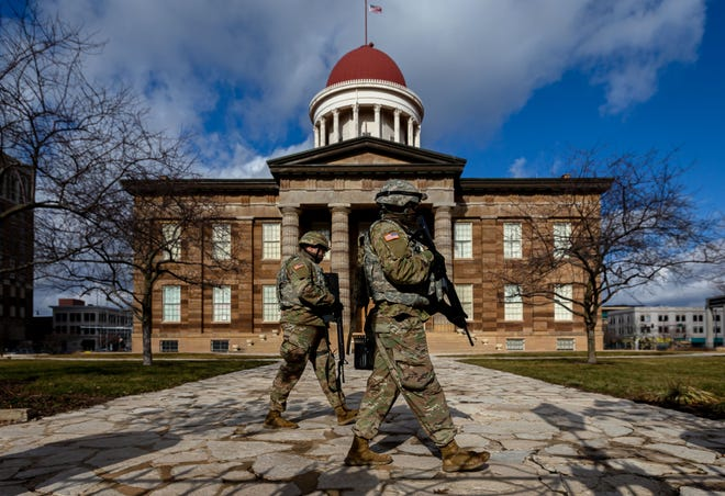 Members of the Illinois National Guard patrol the perimeter of the Old State Capitol, Monday, January 18, 2021, in Springfield, Ill. A heavy police presence remain around the Capitol Complex and other state buildings in light of last week's warning of possible violence planned at all 50 state capitals ahead of the inauguration of President-Elect Joe Biden in Washington, D.C. [Justin L. Fowler/The State Journal-Register]