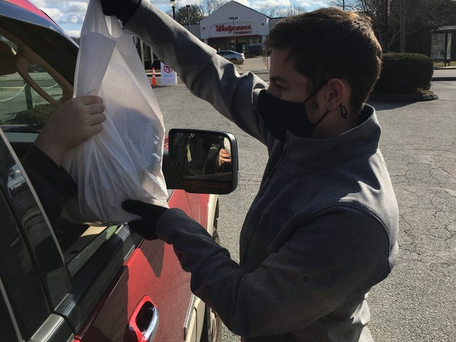 Ryan Fasula of Griswold, 16, hands out donated turkeys in Griswold on Monday, part of a national day of service event on Martin Luther King Day.