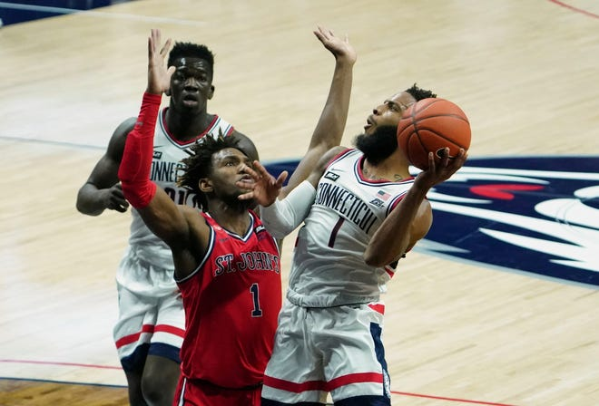 Jan 18, 2021; Storrs, Connecticut, USA; Connecticut Huskies guard R.J. Cole (right) shoots against St. John's Red Storm forward Josh Roberts (middle) in the first half at Harry A. Gampel Pavilion. Mandatory Credit: David Butler II-USA TODAY Sports