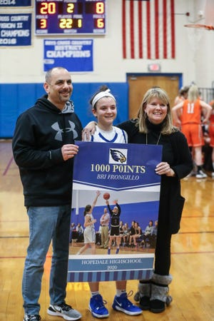 Hopedale's Bri Frongillo, center, stands with father Bill and mother Susan during a ceremony after scoring her 1,000th career point last season.