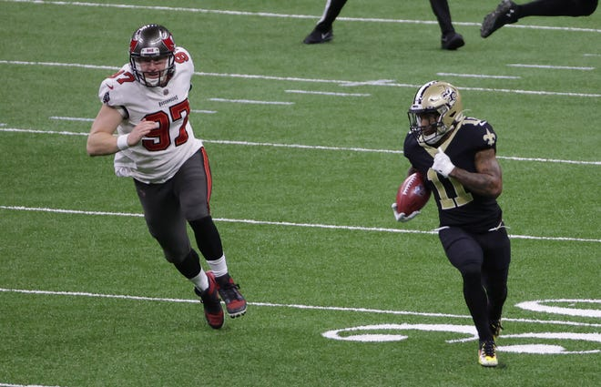 Buccaneers long snapper Zach Triner, left, a former Assumption football standout, chases another former Greyhound,  the Saints' Deonte Harris, on a first-half punt return.