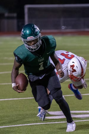 Waxahachie senior quarterback Brandon Hawkins Jr. (1) breaks a tackle during the Indians' 31-28 victory at Lumpkins Stadium against Waco Midway on Nov. 20. Hawkins was voted as the District 11-6A Utility Player of the Year by the coaches in the district.