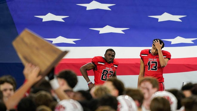 Cedar Hill wide receivers Javien Clemmer (13) and Felton Brisco (83) watch from the bench as Katy players celebrate with the championship trophy after winning the Class 6A Division II state football championship game at AT&T Stadium on Saturday in Arlington. Katy won the game, 51-14.
