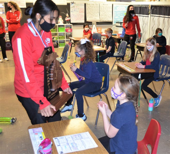 With students at St. Joseph Elementary looking on Monday, St. Philip senior Harleen Deol shows off the Tigers' Division 4 volleyball state championship trophy, which the team won at Kellogg Arena on Saturday.