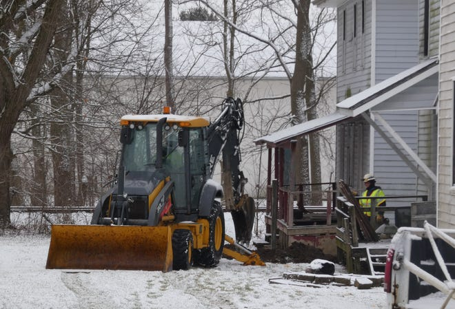 A Columbia Gas crew works outside a home in an alley off North Lane Street near Plymouth Street on Monday morning.