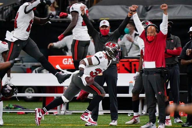 Tampa Bay Buccaneers players and coaches celebrate on the sideline as safety Mike Edwards (32) runs after he intercepted a pass against the New Orleans Saints during the second half of an NFL divisional round playoff football game, Sunday, Jan. 17, 2021, in New Orleans.