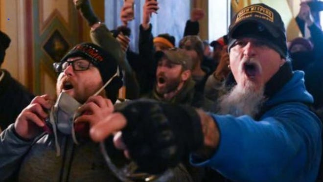 "Indiana resident Jon Schaffer, right, is shown wearing a hat that says ""Oath Keepers Lifetime Member"" inside the U.S. Capitol Building during the Jan. 6, 2021, rioting, according to the FBI. He is now facing six federal criminal charges."