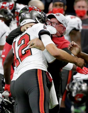 Tampa Bay Buccaneers quarterback Tom Brady (12) hugs head coach Bruce Arians on the sidelines during the second half of an NFL divisional round playoff football game against the New Orleans Saints, Sunday, Jan. 17, 2021, in New Orleans. The Buccaneers won 30-20. (AP Photo/Butch Dill)