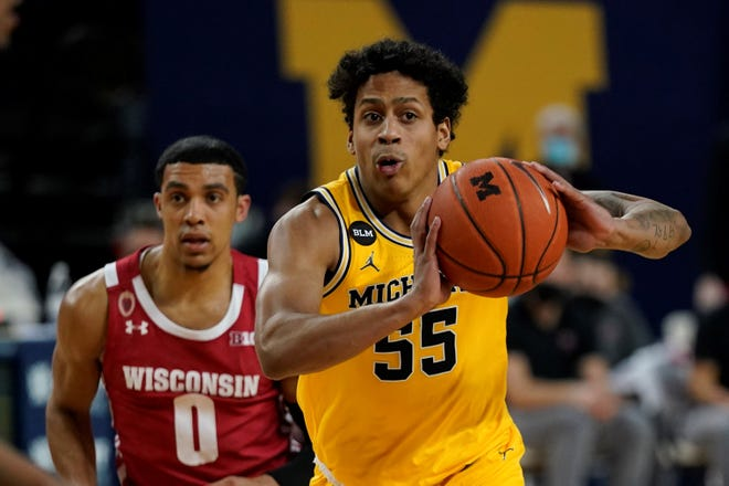 Michigan guard Eli Brooks (55) passes ahead of Wisconsin guard D'Mitrik Trice (0) during the second half of an NCAA college basketball game, Tuesday, Jan. 12, 2021, in Ann Arbor, Mich. (AP Photo/Carlos Osorio)