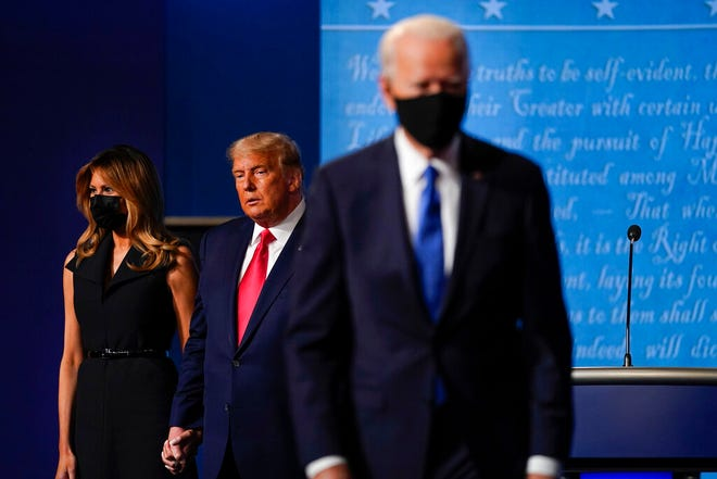 FILE - In this Oct. 22, 2020, file photo first lady Melania Trump, left, and President Donald Trump, center, remain on stage as Democratic presidential candidate former Vice President Joe Biden, right, walks away at the conclusion of the second and final presidential debate at Belmont University in Nashville, Tenn. (AP Photo/Julio Cortez, File)