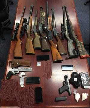 Investigators seized 15 guns along with almost $150,000 worth of drugs, Virginia State Police said in a press release.