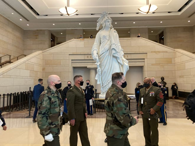 """Personnel evacuate the West front of the U.S. Capitol because of an """"external security threat"""" on Jan. 18, 2021."""