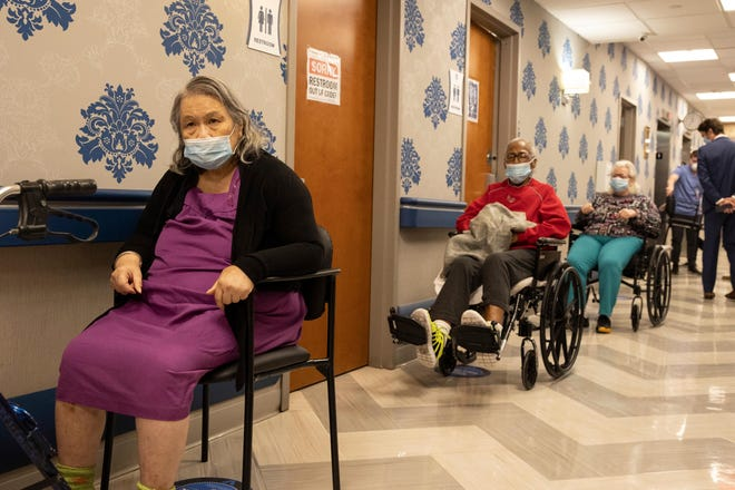 Nursing home residents make a line for the coronavirus disease vaccine at Harlem Center for Nursing and Rehabilitation, a nursing home facility, on Friday, Jan. 15, 2021 in Harlem neighborhood of New York.