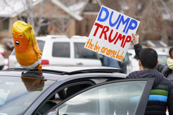 Participants prepare their vehicle calling for the impeachment of President Donald Trump at South High School before a car rally through the streets of downtown Sunday, Jan. 10, 2021, in Denver. More than 150 vehicles were guided by motorists calling for the removal from office of Trump as well as Colorado Republican U.S. Representatives Lauren Boebert and Doug Lanborn for their support of Trump. (AP Photo/David Zalubowski)