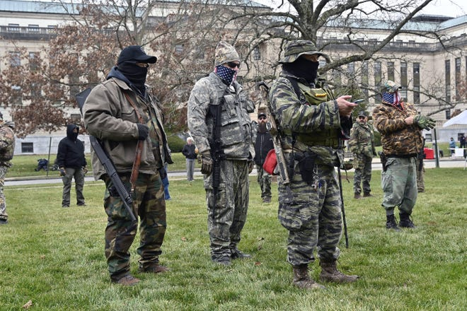 A group of armed protesters listen to speakers during a Jan. 9 rally on the lawn of the Kentucky State Capitol in Frankfort, Ky.