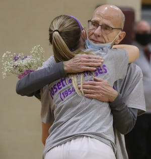 Stow girls basketball coach Bob Podges gets a hug from Lilee Carlson after a ceremony honoring his late wife Josetta before the game against Nordonia on Monday in Stow. [Phil Masturzo/Beacon Journal]