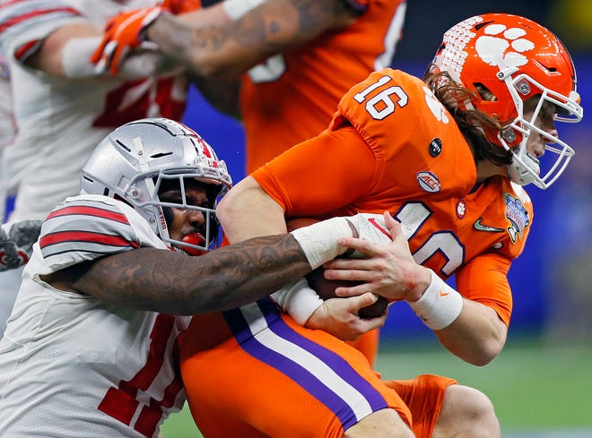 Ohio State Buckeyes defensive end Tyreke Smith (11) tackles Clemson Tigers quarterback Trevor Lawrence (16) on a run in the third quarter during the College Football Playoff semifinal at the Allstate Sugar Bowl in the Mercedes-Benz Superdome in New Orleans on Friday, Jan. 1, 2021.