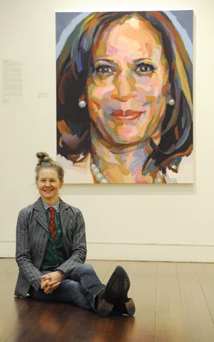 "Provincetown artist Jo Hay sits in front of her oil painting of Vice President-elect Kamala Harris, which is on display at Provincetown Art Association and Museum. The painting is part of ""Persisters,"" an ongoing series of large-scale paintings of women by Hay."