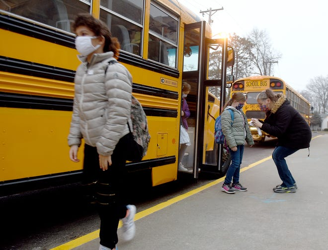 Locust Street Elementary School teacher's aide Julie Mitchell gives students stickers with their bus number Jan. 19 so they can board the correct bus after school is over.