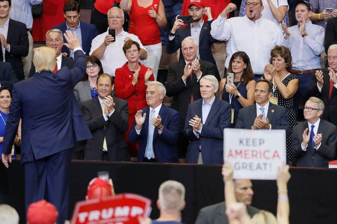 President Donald Trump, left, waves to, from right center, Ohio Gov. Mike DeWine, Kentucky Gov. Matt Bevin, Sen. Rob Portman, R-Ohio, and Rep. Brad Wenstrup, R-Ohio, as he exits a campaign rally in Cincinnati in August 2019.