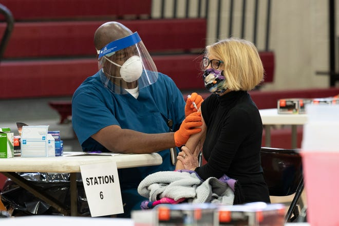 A Lake County teacher gets her COVID-19 vaccine at Tavares High School on Tuesday. [Cindy Peterson/Correspondent]