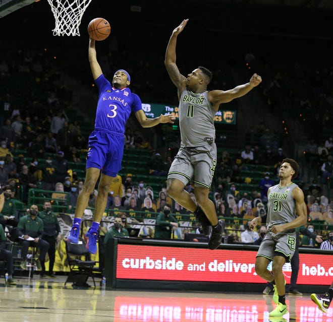 Baylor guard Mark Vital pressures the shot of Kansas guard Dajuan Harris, left, in the first half of Monday's game in Waco, Texas. Baylor held off the Jayhawks for a 77-69 win.