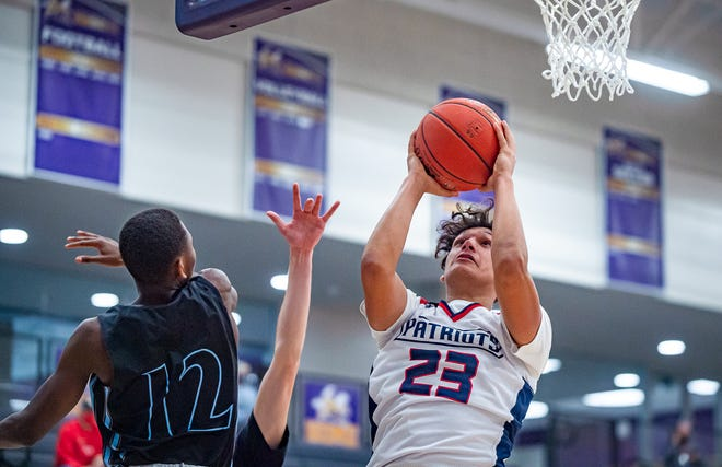 Truman senior Runey Hernandez (23) eludes Oak Park defender Eric Wachira (12) for a basket in Monday's pool play game in the North Kansas City Invitational. Hernandez scored 15 points on his 18th birthday to help the Patriots to a 48-33 win.