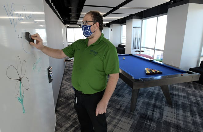 Tower host Robbie Culliton cleans off a whiteboard in the lounge of the VyStar Credit Union headquarters in downtown Jacksonville. Culliton is part of the new Shopability campaign that showcases local businesses that hire people who have intellectual and developmental differences.