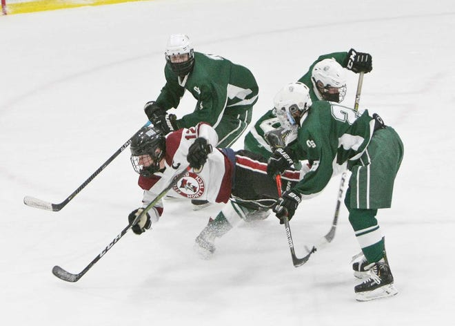 Fitchburg/Monty Tech's Max Beaulac is upended on his way to the net by Oakmont defenders, from left, Ben Mattson, Izak Hannula and Kaleb Jakola during Monday morning's game at the Wallace Civic Center in Fitchburg. Beaulac scored two goals in the Red Raiders' 3-1 win.