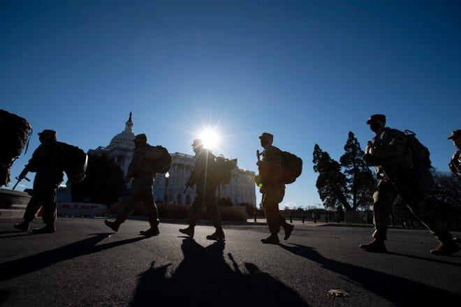 Members of the National Guard walk in line outside of the U.S. Capitol, ahead of President-elect Joe Biden's inauguration ceremony, Tuesday, Jan. 19, 2021, in Washington. (AP Photo/Jose Luis Magana)