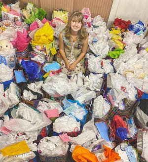 Bethany Taullie sits in a sea of birthday gift bags that were put together as part of her Girl Scout Gold Award project.