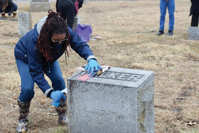 Lauren Cooper cleans a headstone Monday at Mount Muncie Cemetery in Lansing. Volunteers cleaned headstones and placed flags at graves located in historically Black sections of the cemetery, which has been in operation since 1866. The project was organized for Martin Luther King Jr. Day by the Leavenworth County branch of the NAACP. Martin Luther King Jr. Day is designated as a national day of service.