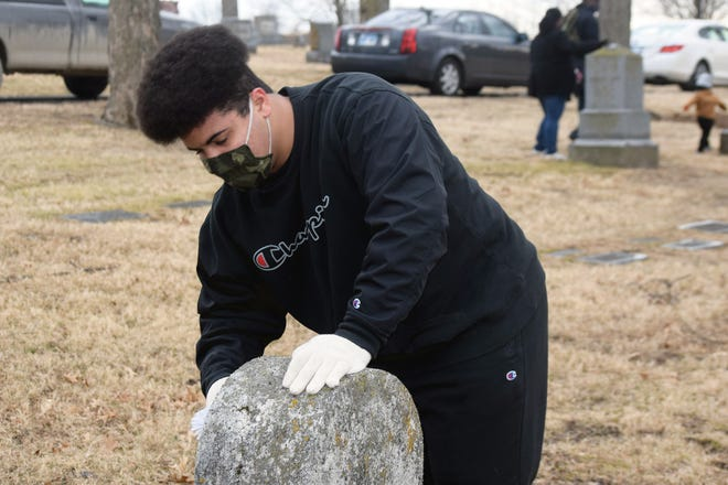 Malaki McCarter cleans a headstone Monday at Mount Muncie Cemetery in Lansing. Volunteers cleaned headstones and placed flags at graves located in historically Black sections of the cemetery, which has been in operation since 1866. The project was organized for Martin Luther King Jr. Day by the Leavenworth County branch of the NAACP. Martin Luther King Jr. Day is designated as a national day of service.