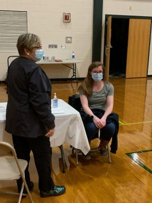 Sutton Firefighter Sierra Renaghan receives the COVID-19 vaccine at Nipmuc Regional High School in Upton.