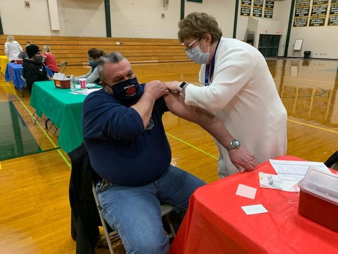 Sutton Fire Chief Matthew Belsito receives the COVID-19 vaccine from Nurse Celestina Kopech at Nipmuc Regional High School in Upton.