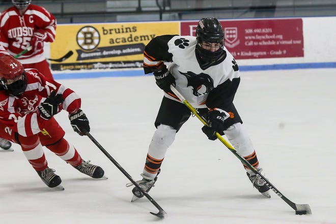 Marlborough junior Mark Evangelous passes the puck, as Hudson junior Nick DiPersio pressures, during the boys hockey game against Hudson at Navin Arena in Marlborough on Jan. 18. Evangelous scored a goal in the Panthers 2-0 win over Nashoba on Tuesday.
