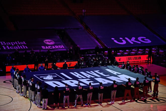 """Miami Heat and Detroit Pistons players hold a """"I Have a Dream"""" banner midcourt during the playing of """"Lift Every Voice and Sing"""" prior to the game Monday at American Airlines Arena."""
